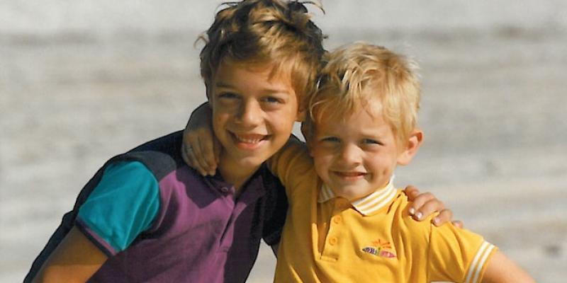 two young boys with their arms around each other smiling for the camera